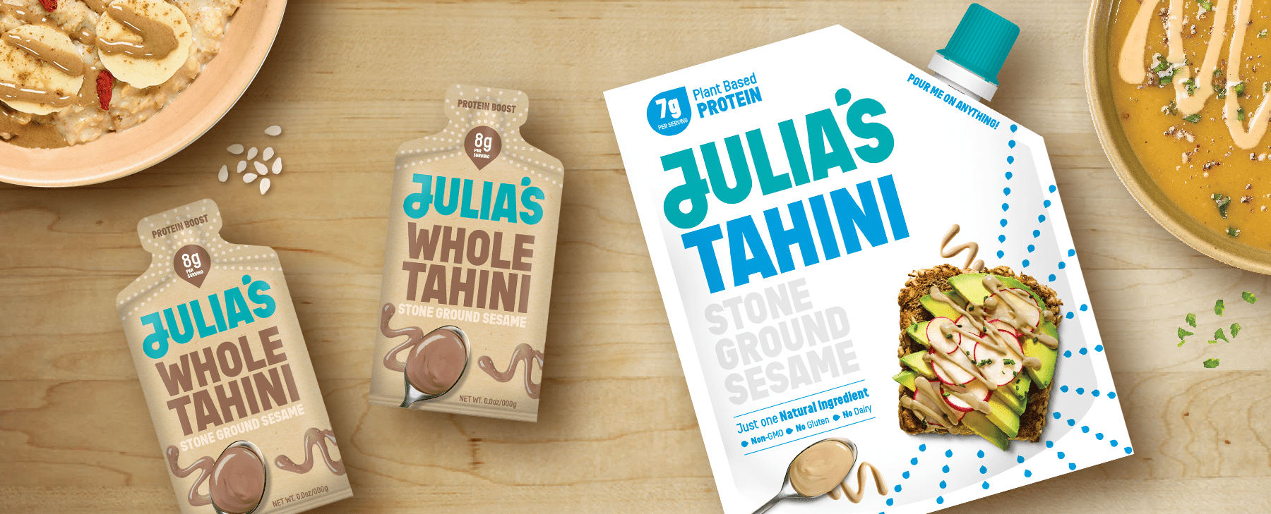 Julia's tahini sachets in brown and larger pouch in white sitting on a close up of a kitchen table with ingredients surrounding them